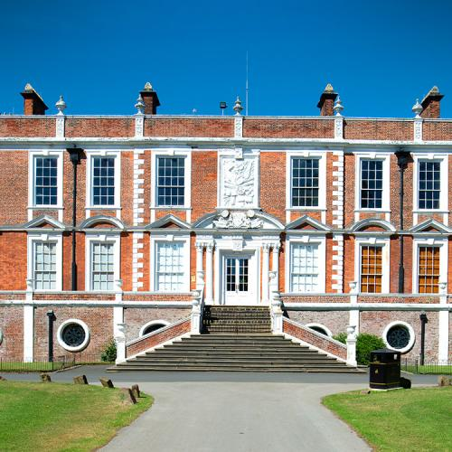 Croxteth Hall by day in front of a blue sky with green grass in front of the hall showing a straight path to the entrance