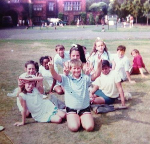 school children in a vintage photograph relaxing on the grass in front of the back of croxteth hall