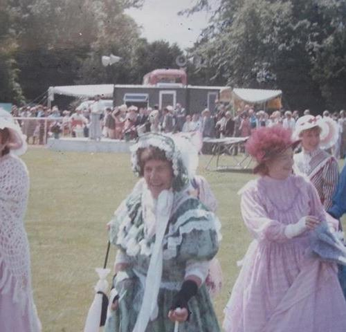 one lady in pink edwardian fancy dress and one lady in a green edwardian fancy dress walking across the grounds