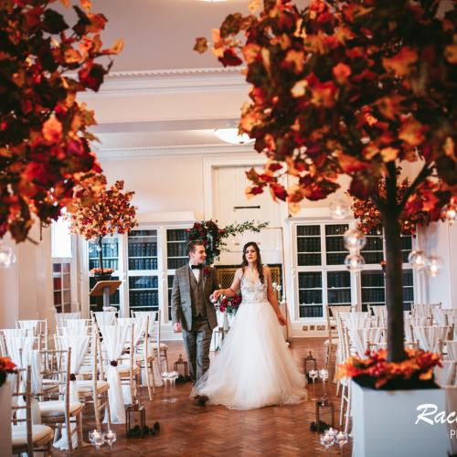 two larhe pots of flowers on left and right with red flowers, bride and groom in middle of white chairs in front of a wall of library books
