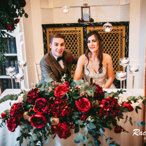 bridge and groom sitting at a table with red roses in front of them and library boks on the wall